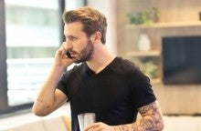 A young man with a black short sleeve shirt and arm tattoos talks on the phone with a serious look on his face